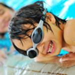 CHłopiec podczas nauki pływania się śmieje
