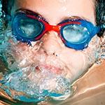 Chłopiec nurkuje podczas zajęć w szkole pływania